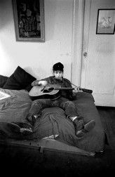 Bob Dylan playing guitar and harmonica on his bed, NYC 1961